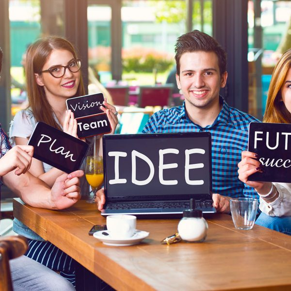 Group of young people sitting at a cafe, holding electronic gadg
