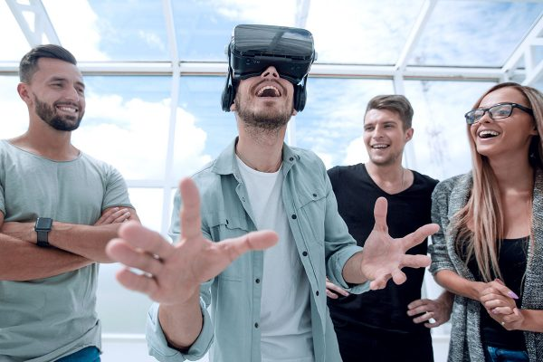 Photo of young man standing in the office in VR headset experiencing opportunities of gaming, pointing upwards as if trying to touch object he sees